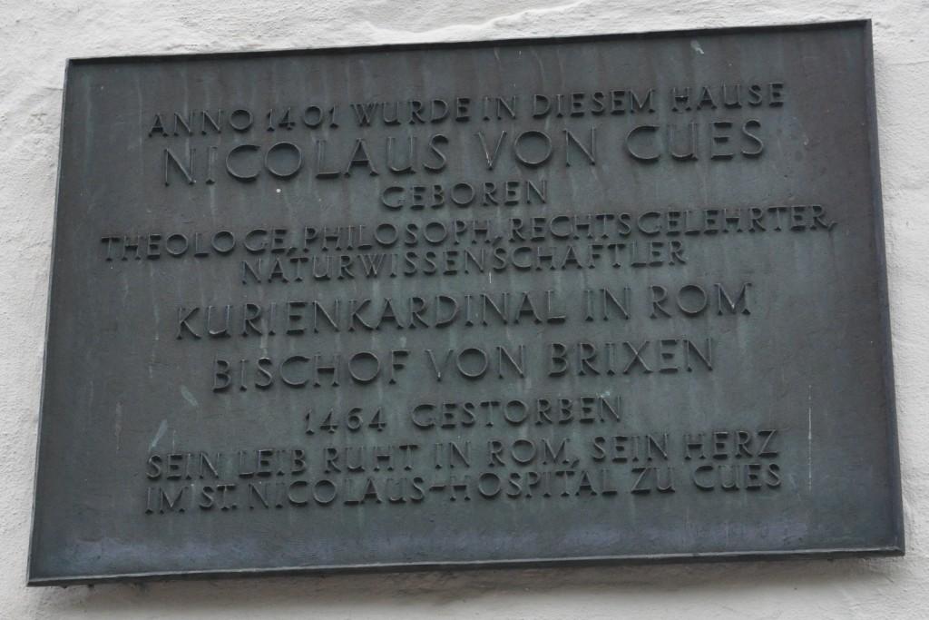 """Tablica na domu rodzinnym Kuzańczyka: """"W roku 1401 w tym domu narodził się Mikołaj z Kuzy - teolog, filozof, prawnik, przyrodoznawca, kardynał, biskup Brixen. Zmarł w 1454 roku. Jego ciało spoczywa w Rzymie, jego serce w Szpitalu św. Mikołaja w Kues"""""""